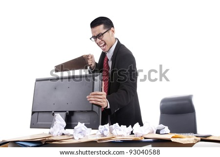 Frustrated asian businessman sawing his computer on white background - stock photo