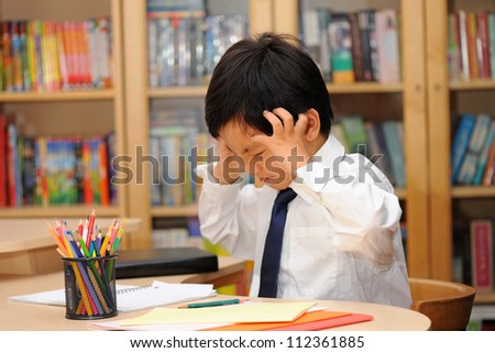 Frustrated Asian schoolboy in school uniform ( white shirt and tie ) doing homework - stock photo