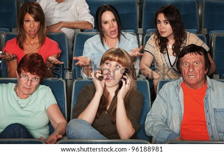 Frustrated audience with rude woman on phone - stock photo