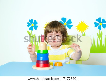 Frustrated baby learning how to build pyramid toy in kindergarten or day care, intellectual development  - stock photo