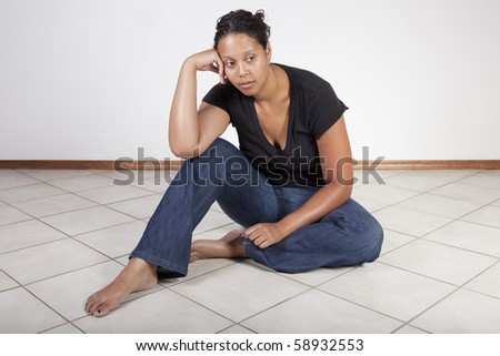 Frustrated black woman sitting on floor, contemplative. - stock photo