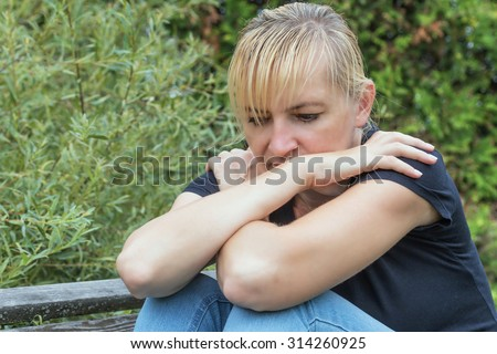 Frustrated blonde woman is in black shirt sitting on the wooden bench outdoors. Her hands are resting on her knees and touches cross their arms. - stock photo