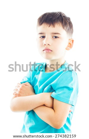 Frustrated boy looking up with an offended look, his arms crossed - stock photo