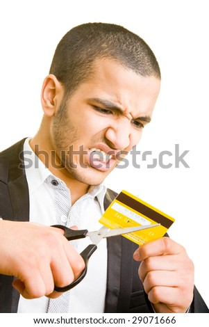 Frustrated business man cutting a credit card - stock photo