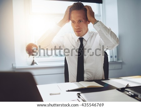 Frustrated business man looking at laptop holding his hands to his head in frustration - stock photo