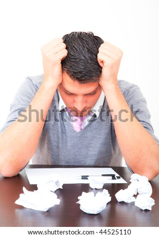 Frustrated business man on desk with paper and pen being stressed
