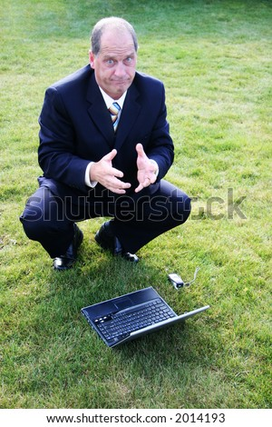 Frustrated Business man outdoors in the grass - stock photo