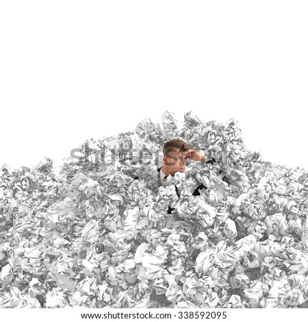 Frustrated businessman buried by balls of paper - stock photo