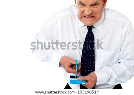 Frustrated businessman cutting his credit card. Extremely disappointed - stock photo
