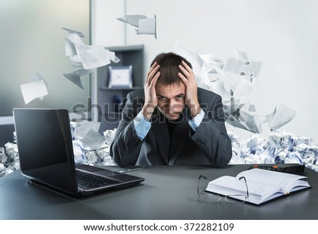 Frustrated businessman holding his head sits in the office - stock photo
