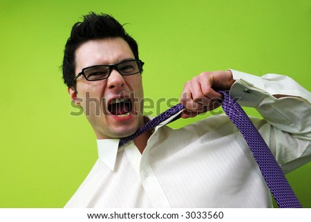 Frustrated businessman screams and pulls at his tie - stock photo