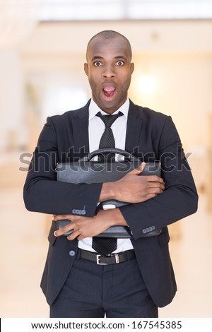 Frustrated businessman. Shocked young African man in full suit holding a bag in his hands and keeping mouth open while looking at camera