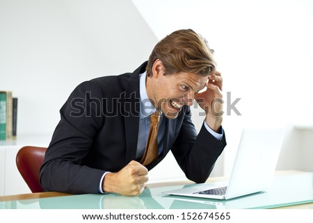 Frustrated Businessman Sitting At Desk In Office Using Laptop With Hand To His Head. - stock photo