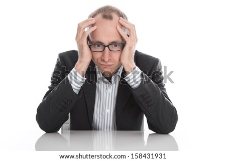 Frustrated businessman wearing glasses sitting at desk with head in hands isolated on white background - stock photo