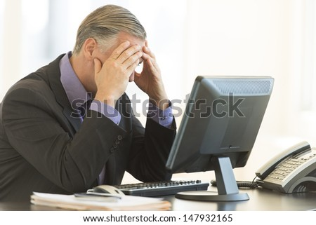 Frustrated businessman with head in hands sitting at office desk - stock photo