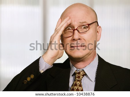 Frustrated businessman with his glasses askew and a hand to his forehead - stock photo