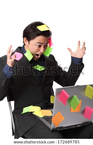 Frustrated businessman with lap top and post it notes all over him. White background. - stock photo