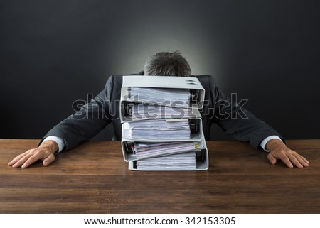 Frustrated businessman with lot of files on desk against gray background - stock photo