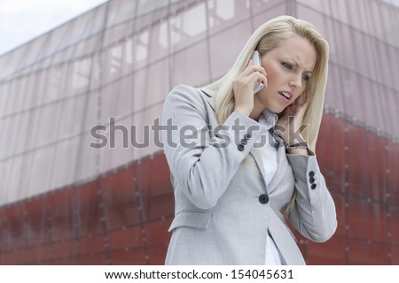 Frustrated businesswoman in suit conversing on cell phone against office building - stock photo