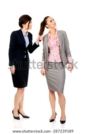 Frustrated businesswoman pulls her friends hair. - stock photo