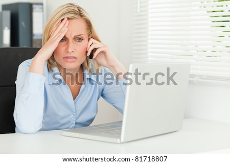 Frustrated businesswoman sitting in front of her notebook on phone in her office