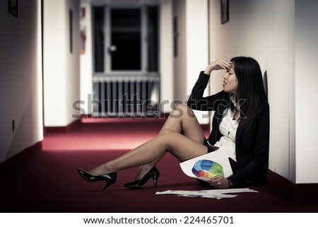 Frustrated Businesswoman sitting on the corridor of the hotel. - stock photo