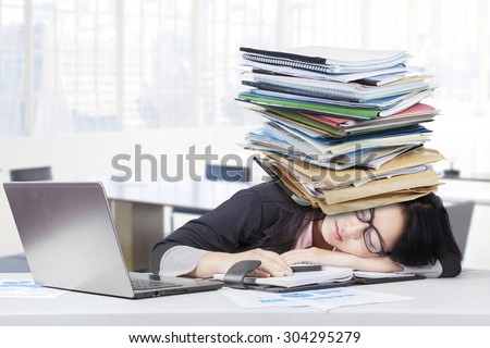 Frustrated businesswoman sleeping in the office with paperwork on head and laptop on the table - stock photo