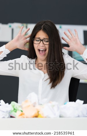 Frustrated businesswoman throwing a tantrum screaming and raising her hands in the air as she looks at a pile of crumpled paper on her desk as she battles for a solution to a problem - stock photo