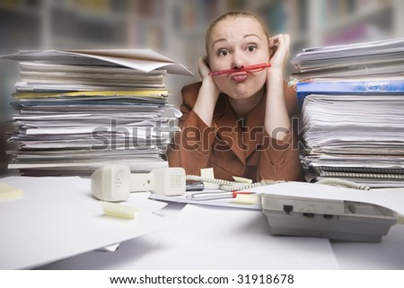 frustrated businesswoman with pencil under nose at the office