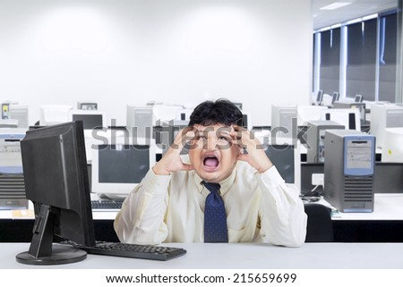Frustrated fat businessman shouting alone in office - stock photo