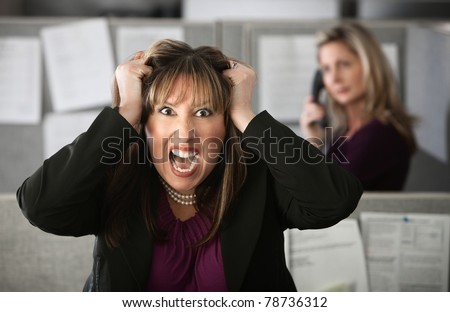 Frustrated female office worker in a cubicle pulls her hair - stock photo