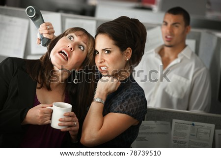 Frustrated female office worker strangles her coworker with a telephone cord - stock photo