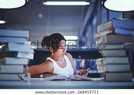 Frustrated female student sitting at the desk with a huge pile of study books in university library, young asian college student at hard exam preparation in study hall looking tired and weary - stock photo