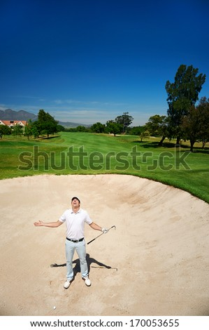 frustrated golfer in sand bunker on golf course loosing his temper - stock photo