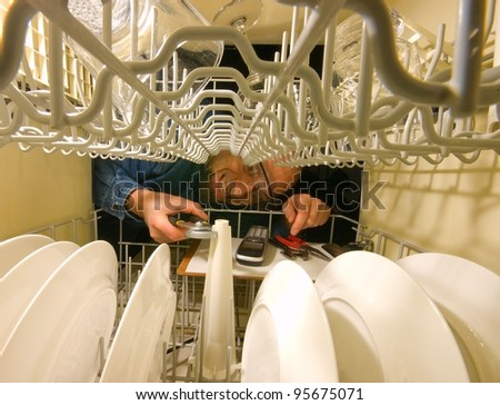Frustrated grimacing service technician trying to fix a dish washer. Horizontal picture from inside the machine. - stock photo