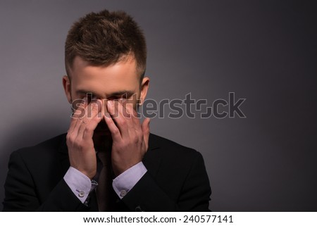 Frustrated handsome. Depressed young businessman in formalwear holding hands on eyes thinking of bad news while stranding against grey background - stock photo