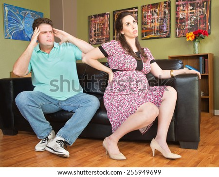 Frustrated husband next to pregnant wife with backache - stock photo