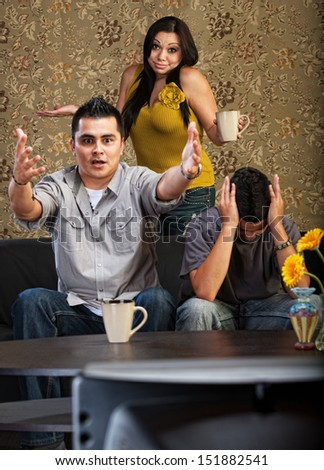 Frustrated Latino family indoors in front of television together - stock photo