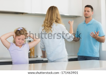 Frustrated little girl covering ears while parents arguing in kitchen - stock photo