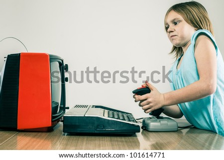 Frustrated little girl on video gaming joystick in front of vintage TV set