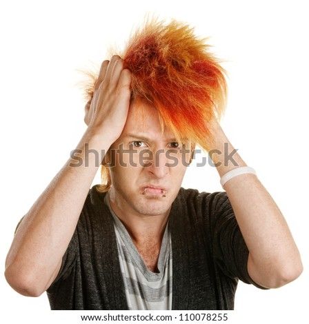 Frustrated male teenager in mohawk pulling his hair - stock photo
