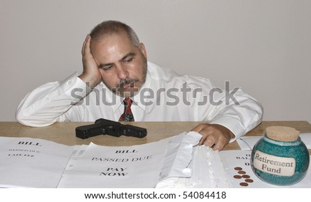 Frustrated man in despair over economy mounting bills and unpaid debts contemplating suicide - stock photo