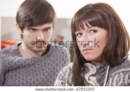 frustrated man looking at unhappy woman in apartment - stock photo
