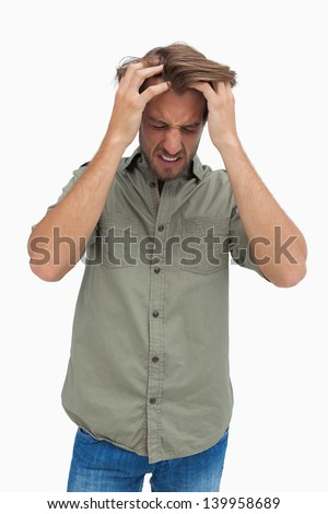 Frustrated man pulling his hair and looking down on white background - stock photo