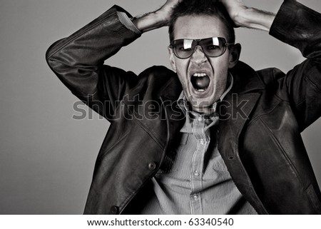 Frustrated man pulls his hair out in anger - grain added - stock photo