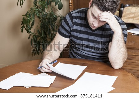 Frustrated man sits in the kitchen  - stock photo