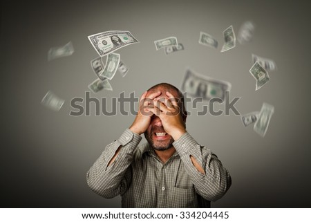 Frustrated man. Taxes and debts. Expressions, feelings and moods. Falling dollars.