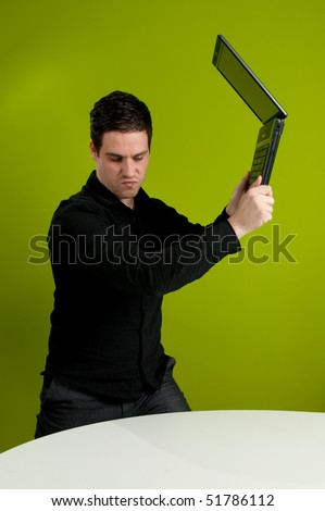 Frustrated man trashing his laptop on table - stock photo