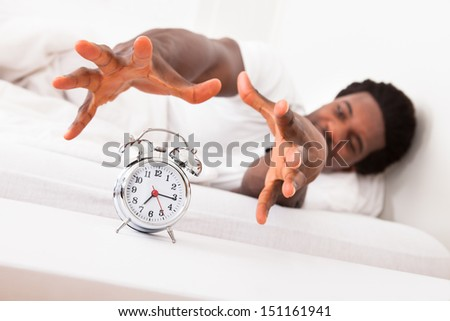 Frustrated Man Trying To Catch Is Alarm Clock While Relaxing On His Bed - stock photo