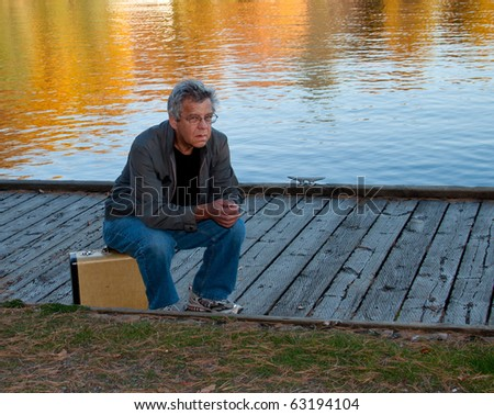 Frustrated man waiting and sitting on a suitacase - stock photo